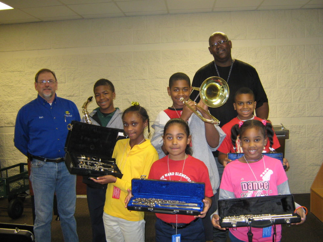 Ken Prine from Insta-Cash Pawn poses with staff and young members of the Longview Texas Boys & Girls Club. The children hold various band instruments.