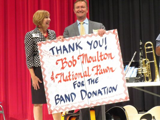 "Bob Moulton of National Pawn Receiving a Thank You Banner from a school representative. The banner reads, ""Thank You Bob Moulton & National Pawn for the band donation."" The banner is also signed by the band students. Clicking this image will open it in a pop-up window."